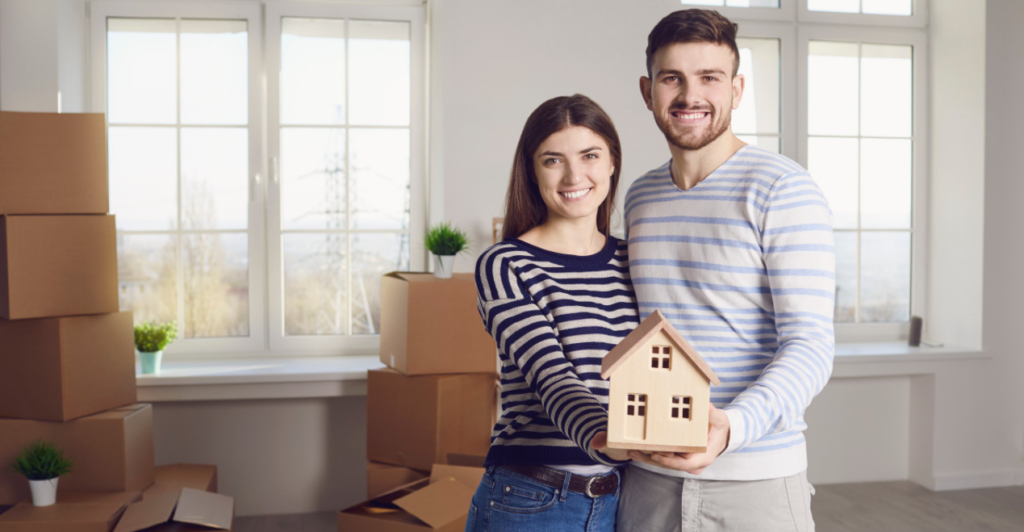 couple holding a miniature house model; steps to selling a house by owner
